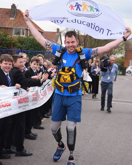 Amputee Duncan Slater carries the Unity Education Trust flag aheasd of his Marathon des Sables chall