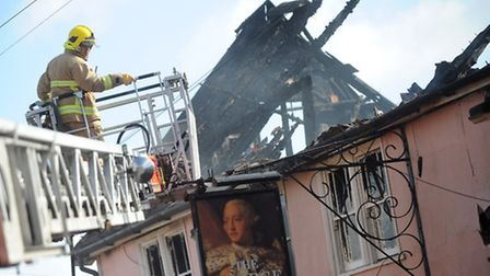 A Fire Fighter from Leiston and Aldeburgh works on damping down the fire at The George Pub in Wickha