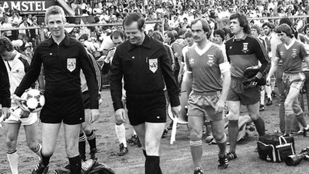 The match officials look relaxed, but Mick Mills has an apprehensive frown as he leads Ipswich out f