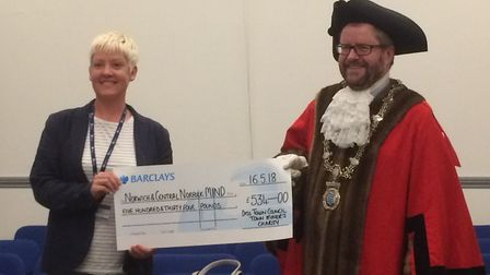 Newly elected mayor of Diss, Trevor Wenman presenting a representative from the charity Tearfund wit