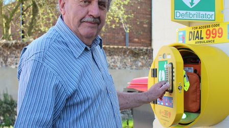 Chairman of Winfarthing Parish council, Jim Collins checking the village defibrillator, Picture: Zac