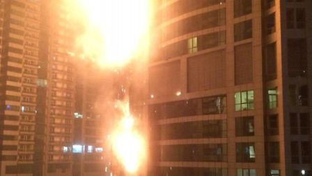 This photo provided by Rhea Saran shows flames coming from a high rise tower in Dubai's marina distr