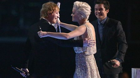 Ed Sheeran (left) greets Rita Ora as he collects his Best Male Solo Artist during the 2015 Brit Awar