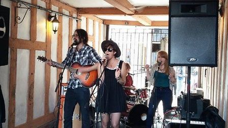Mischa Pearson (centre) and her band Busking For Breakfast performing live