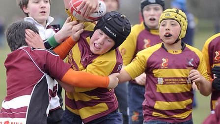 Hadleigh, in burgundy and white, and Ipswich YM, in burgundy and yellow, play a match in the Under 1