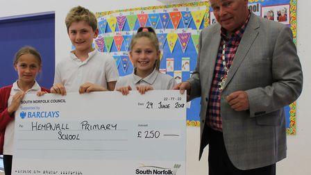 South Norfolk Council chairman John Overton presents £250 to pupils from Hempnall Primary School. Ph