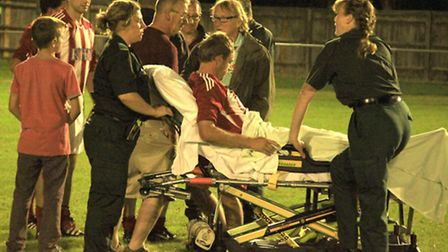 Felixstowe & Walton United striker Danny Smy about to be loaded into an ambulance after damaging his