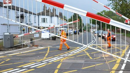 Engineers checking the level crossing after carrying out repairs after it was struck by a skip lorry