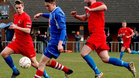 Leiston striker Josh Mayhew attempts to get away from Harrow defenders Anthony Page (left) and Micha