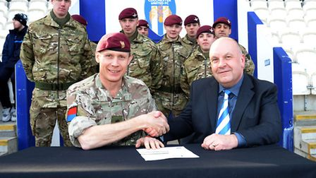 Colonel Gary Wilkinson, Commander of Colchester Garrison, signs the document with Colchester United