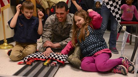 Cameron and Alexis Fisher, 8-year-old twins, cheer on boxcars with their father, Tech. Sgt. Christop