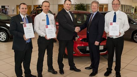 Ashley Freeston, centre, Nissan GB after sales performance manager, presents Hammond Nissan's hat-tr