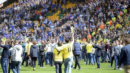 Norwich fans invade the pitch after their win at Carrow Road, with disappointed Ipswich fans looking