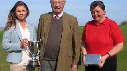 Suffolk Ladies' champion, 19-year-old Lottie Whyman, holds the Churchman Challenge Cup, with sponsor