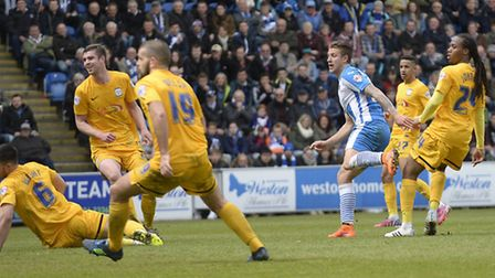 George Moncur watches his shot hit the back of the net and keep Colchester in League One