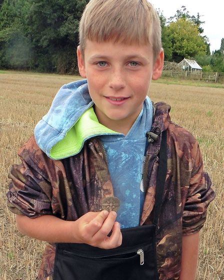 George Bunn, 11, the youngest detectorist taking part, with a silver technician's badge from the Sec