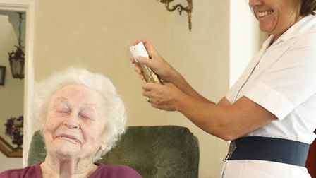 Care worker nurse helping an elderly client with her hair (stock image)