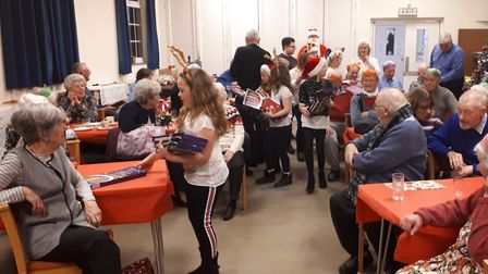 Young people from Harleston Junior Club help out at the Christmas party for the town's pensioners.