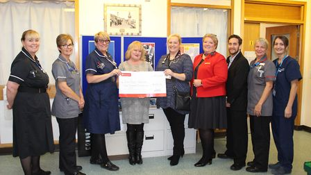 Lynne Ainge is pictured centre behind the cheque, with Carole Wall and members of the Sepsis project