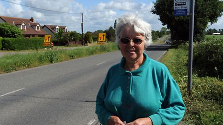Zena Gravener is cutting the central grass verge on Old London Road, Copdock, with a sickle. Dorothy