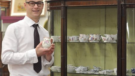 Associate Director Marc Winter holds some Lowestoft Porcelain from the 18th century that is going up