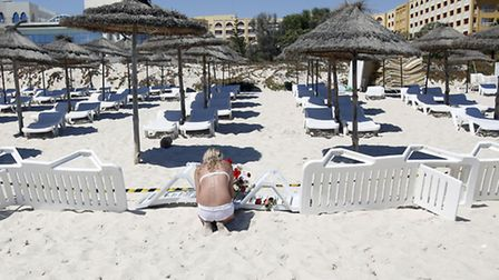 A young woman lays flowers at the scene of a shooting in Sousse. (AP Photo/Darko Vojinovic)