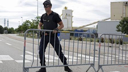 A police officer blocks the road leading to a plant where an attack took place in Saint-Quentin-Fall