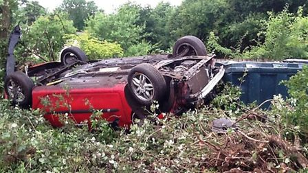 A car on its roof after crashing in to a garden at Bulmer Tye