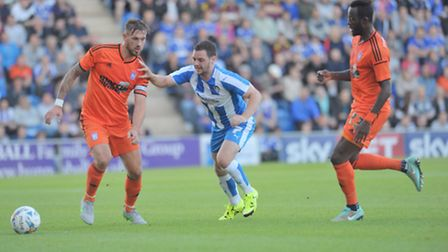 Luke Chambers holds off Drey Wright with Town trialist Larsen Toure watching on.