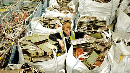 A member of staff at N2S bagging up scrap computer components ready for further destruction and recy