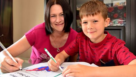Louise Chalklen and her son Aaron have fun fun colouring an action hero book.