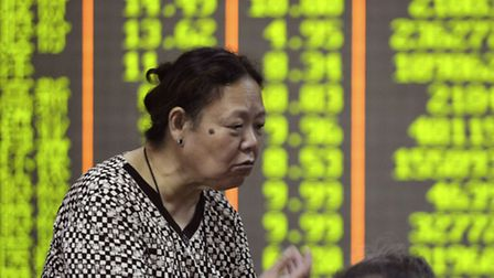 A Chinese stock investor gestures near a board with green numbers representing falling stocks at a b