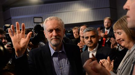 Jeremy Corbyn (left) prepares to take to the stage after he was announced as the Labour Party's new