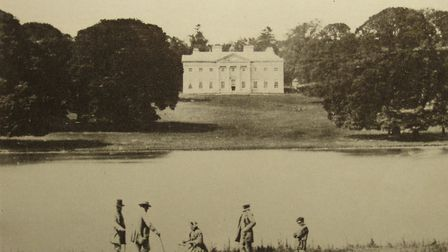 Members of the Holt-Wilson family stand across the water from Regrave Hall in a photograph taken by