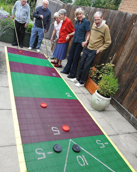 Age UK service users at the Denny Centre in Diss playing with their new deck shuffleboard before the