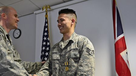 Airmen congragulate Senior Airman Aaron Thomas, 48th Contracting Squadron contracting specialist, at