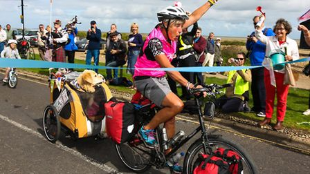 Maggie Scorer celebrates the end of her ride as she crosses the finish line outside the Wentworth Ho