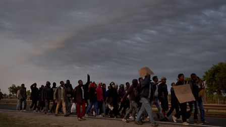 Migrants march toward the Channel Tunnel during a demonstration in Calais. (AP Photo/Emilio Morenat