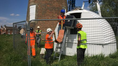 Preparing to attach the renovated cap to the crane sling ready for lifting to the top of Billingford