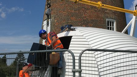 Attaching the renovated cap to the crane sling ready for lifting to the top of Billingford Mill, nea