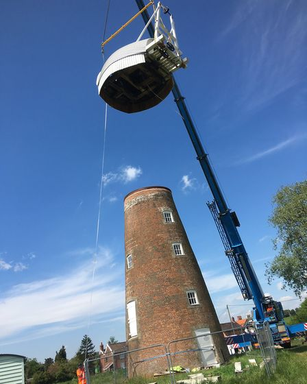 The renovated cap is lifted by crane ready to be re-attached into place on top of Billingford Mill,