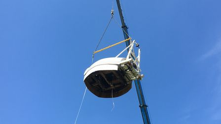 The renovated cap is swung high into above Billingford Mill, near Diss, ready to be gently lowered i