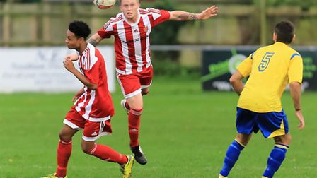Felixstowe's Connor Field heads clear, with Felixstowe's Kyrain Andrews, left and Newmarket's Scott