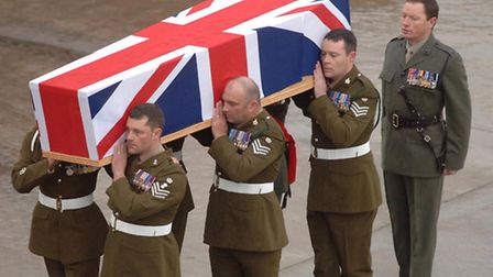 Military personnel carrying a coffin containing the body of Staff Sergeant Sharron Elliott, 34, from