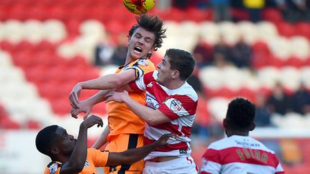 Alex Gilbey battles in the air during the first half at Doncaster