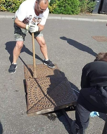Dean Fowles and Rob Payne prising open manhole covers in their search for three lost ducklings in Di