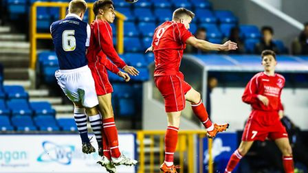 Woodbridge Towns Calum Sinclair and George Mrozek battle in the air with James White during the Mill