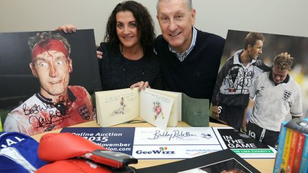 Terry Burtcher signs photos of himself for the Sir Bobby Robson charity auction. Terry is pictured w