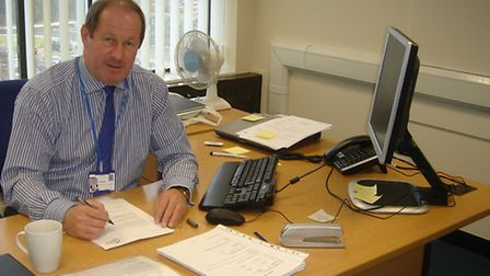 Tim Passmore at his desk as Police and Crime Commissioner