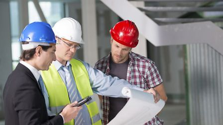 Construction team reviewing blueprints together. Library image.
